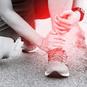 Runner touching painful twisted or broken ankle. Athlete runner training accident. Sport running ankle sprained sprain cause injury.